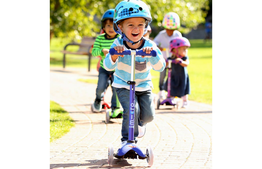 Kid riding a Mini Micro Deluxe Scooter at a park